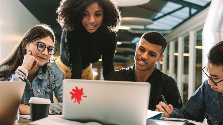 Eine Gruppe junger Studenten oder Schüler schaut sich gemeinsam etwas am Laptop an.